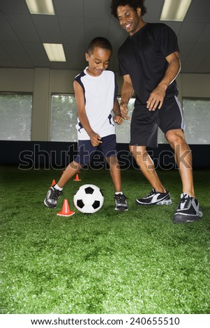 Man and Boy Playing Soccer - stock photo