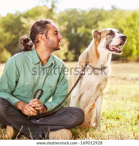 Man and central Asian shepherd walk in the park. He keeps the dog on the leash - stock photo