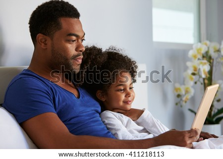 Man and daughter sitting in bed watching computer, waist up