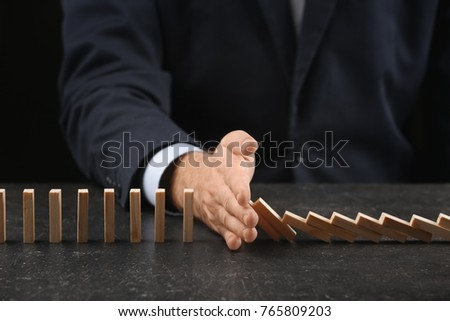 Man and domino pieces on table. Management concept