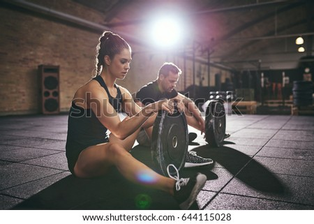 Man and female in sportswear doing exercises with round bars while sitting on floor in gym.