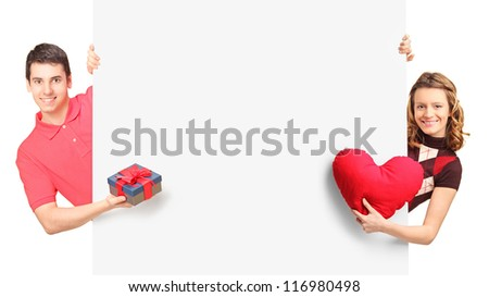 Man and female with gift and red heart posing behind a panel, isolated on white - stock photo