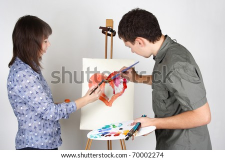 man and girl holding brushes and palette, painting red heart - stock photo
