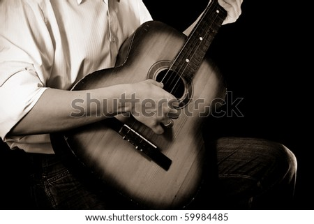 man and guitar at black - stock photo