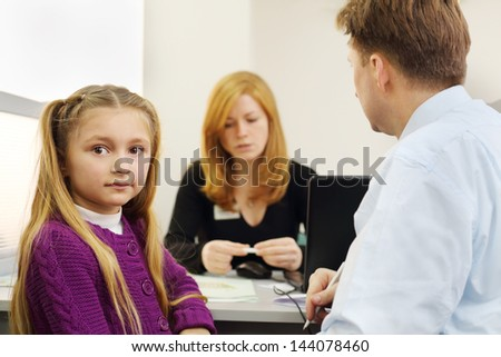 Man and her little daughter sit in office of realtor, girl looks at camera. Focus on man and girl. - stock photo
