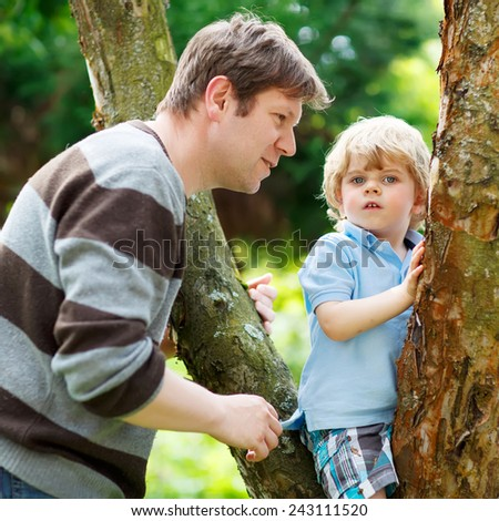 Man and his adorable little child having fun in forest. Funny kid boy climbing on tree. Family leisure outdoors, on warm summer day. - stock photo