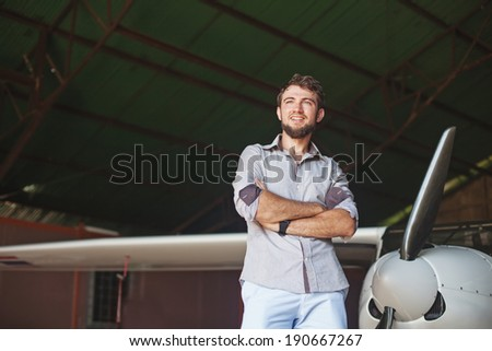 man and his airplane in hangar