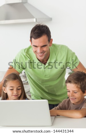 Man and his children using a laptop together in the kitchen - stock photo