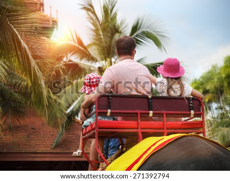 Man and his daughters riding on the back of elephant in Thailand - stock photo