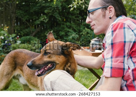 Man and his dog rest in the garden at summer day