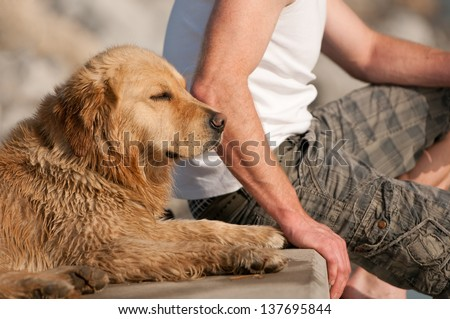 man and his dog sitting on a sunny day on a step - stock photo