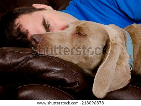 Man and his dog sleeping  on the couch - stock photo