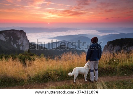 Man and his faithful friend the dog admire the mountain scenery in the campaign at sunrise - stock photo