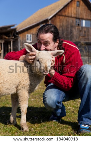 Man and lamb in front of a farm - stock photo