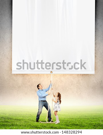 Man and little girl pulling banner. Place for text - stock photo