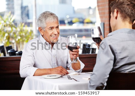 Man and senior man drinking red wine in a restaurant