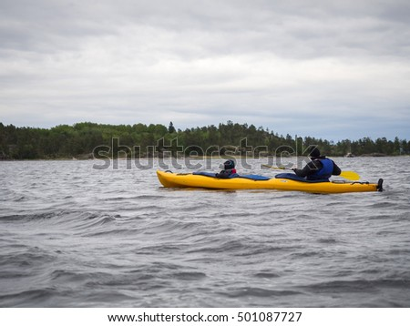 Man and small kid in a rowing kayak on a large Ladoga lake in Karelia, northern Russia