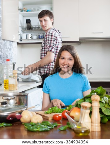 Man and smile woman cooking in domestic kitchen