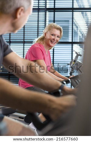 Man and smiling senior woman riding exercise bikes in health club