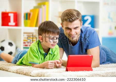 man and son kid playing with tablet computer - stock photo
