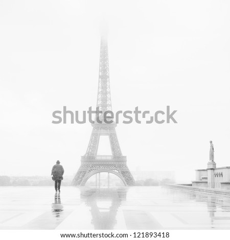 Man and the Eiffel Tower, rain and fog. - stock photo