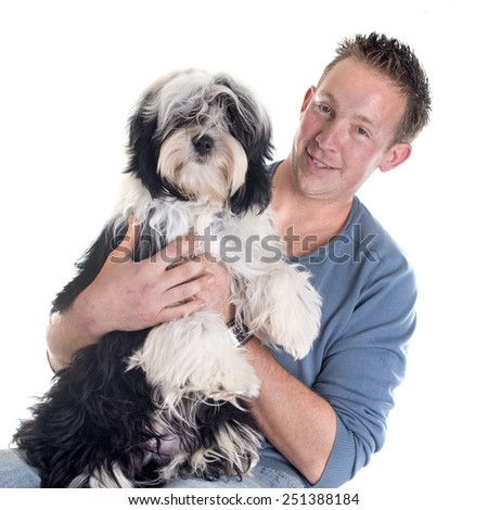 man and  tibetan terrier in front of white background