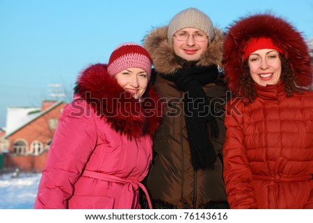 man and two women standing on outdoors in winter near to house, friends - stock photo