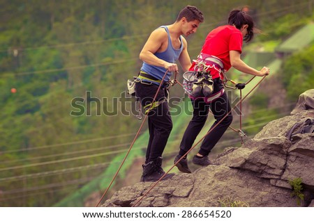 man and woman about to start rapelling down mountain - stock photo