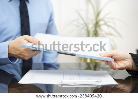 Man and woman are exchanging contract or document - stock photo