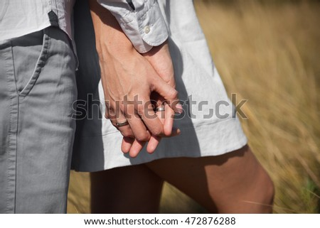 Man and woman are holding hands and showing rings Side view photo. Married couple has a walk in the countryside. They are holding hands and stand in the middle of the sun-drenched field.