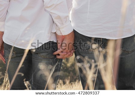 Man and woman are holding hands Loving couple has a walk in the countryside. They hold hands and think about their future. Both of them are dressed in white shirts.