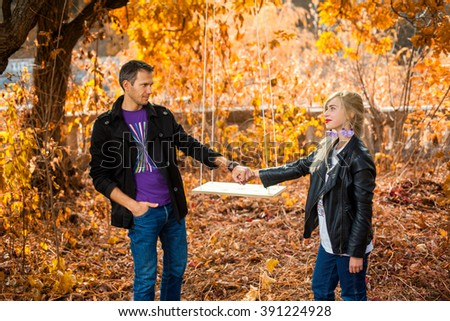 Man and woman are holding their hands in the park