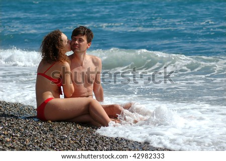 Man and woman are kissed sitting on beach