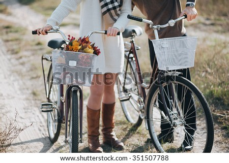 man and woman are on the field and lead the way in the hands of bicycles in the bicycle basket is a bouquet of autumn leaves and red flowers - stock photo