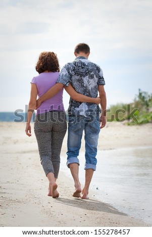 Man and woman are walking on the beach, back view