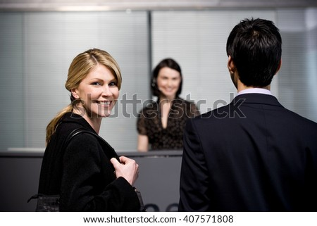 Man and woman arrive at office reception for a business meeting - stock photo