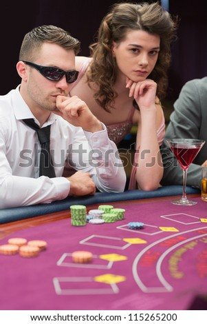Man and woman at poker table in casino - stock photo