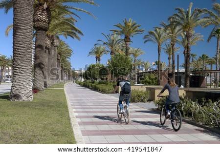 Man and woman bicycling in a promenade