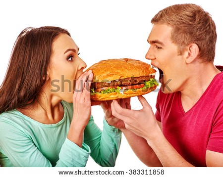 Man and woman biting big hamburgers . Fast food concept. Isolated. - stock photo