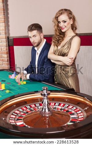 Man and woman by roulette table at casino - stock photo