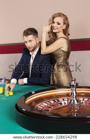 Man and woman by the roulette table at casino - stock photo