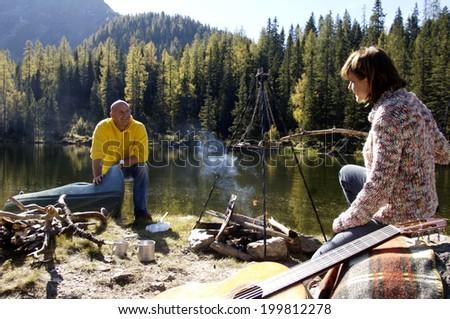 Man and woman camping at lake - stock photo