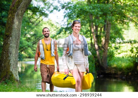 Man and woman carrying canoe to forest river - stock photo