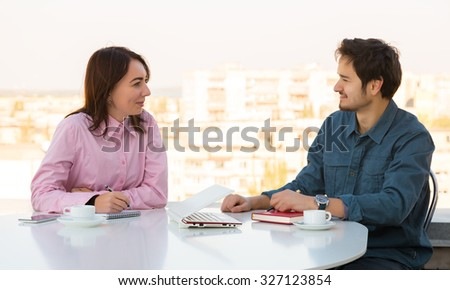 Man and Woman Casual Clothing Sitting at White Round Table with Coffee Mugs Laptop Notepads and Telephone Discussing Smiling Making Hand Notes Urban Landscape on Background - stock photo