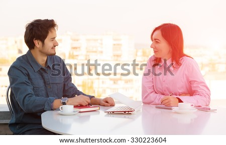 Man and Woman Casual Clothing Sitting at White Round Table with Coffee Mugs Laptop Notepads and Telephone Discussing Smiling Making Hand Notes Urban Landscape on Background Shining Sun Back-light - stock photo
