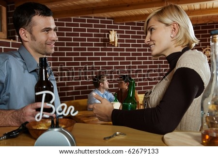 Man and woman chatting in bar, smiling at each other, young couple in background.? - stock photo