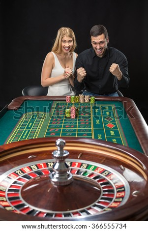Man and woman cheering at roulette table in casino - stock photo