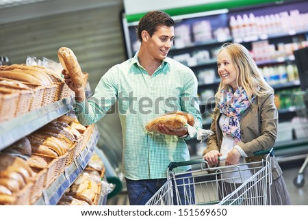 Man and woman choosing bread during shopping at bakery supermarket store - stock photo