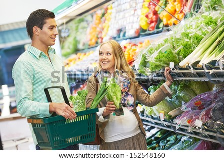 Man and woman choosing fresh fruits or greens during shopping at bakery supermarket store - stock photo