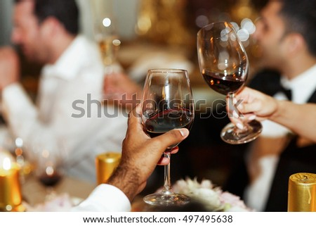 Man and woman clang glasses with red wine